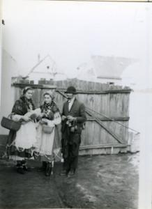 Poklade. Pokladne maškare. Dvije djevojke u narodnoj nošnji i s njima maškare sa zvoncima. Folklorna građa Otoka i Nijemaca, 1965.